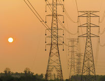 Silhouette of electricity pylons and lines. Stock Photos