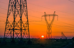 Silhouette electricity pylons Stock Images