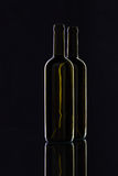 Silhouette of elegant and very old wine bottles on a glass desk Royalty Free Stock Image