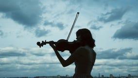Silhouette of elegant violinist plays on balcony on beautiful background. Silhouette of elegant violinist plays melody on balcony on beautiful background. Slowly stock footage