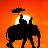 Silhouette elephant with tourist at sunset Royalty Free Stock Images