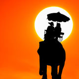 Silhouette elephant with tourist at sunset Stock Image