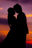 Silhouette of Embracing Asian Bride and Groom at Sunset Royalty Free Stock Image