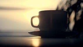Silhouette en gros plan et foncée d'une tasse de thé ou café, sur une soucoupe, sur le fond du lever de soleil, aube, dans les ra banque de vidéos