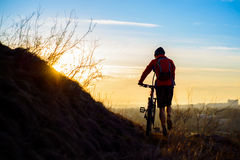 Silhouette of Enduro Cyclist with Mountain Bike on the Rocky Trail at Sunset. Active Lifestyle Concept. Space for Text. Royalty Free Stock Image