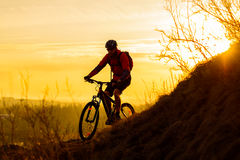 Silhouette of Enduro Cyclist Riding the Mountain Bike on the Rocky Trail at Sunset. Active Lifestyle Concept. Space for Text. Royalty Free Stock Images