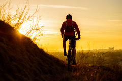 Silhouette of Enduro Cyclist Riding the Mountain Bike on the Rocky Trail at Sunset. Active Lifestyle Concept. Space for Text. Royalty Free Stock Photos