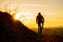 Silhouette of Enduro Cyclist Riding the Mountain Bike on the Rocky Trail at Sunset. Active Lifestyle Concept. Space for Text. Stock Image