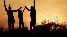 Silhouette, enfants heureux avec la mère et père, famille au coucher du soleil Photographie stock libre de droits
