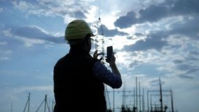 Silhouette of engineer electricity talking and use phone during sunset stock footage