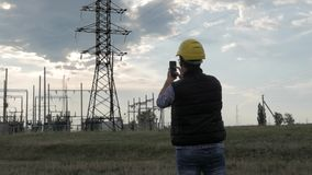 Silhouette of engineer electricity talking and use phone during sunset stock video footage