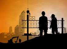 Silhouette engineer looking blueprint in a building site over Bl Royalty Free Stock Image