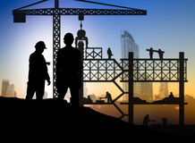 Silhouette engineer looking construction worker in a building si Stock Photo