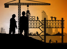 Silhouette engineer looking construction worker in a building si Stock Image