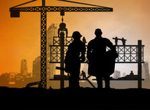 Silhouette engineer looking construction worker in a building si Stock Photos
