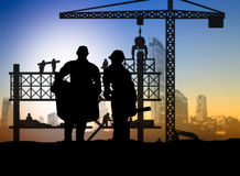 Silhouette engineer looking construction worker in a building si Stock Images