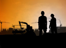Silhouette engineer looking Loaders and trucks in a building sit Royalty Free Stock Photo