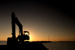 Silhouette of Excavator loader at the sunset beach behind Royalty Free Stock Photography
