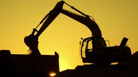 Silhouette of an excavator that loads sand into a truck at sunset. Concept construction and heavy industry, machine will