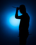 Silhouette Expressive young drummer with drum stick on a blue background Royalty Free Stock Images
