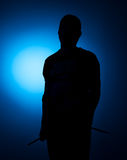 Silhouette Expressive young drummer with drum stick on a blue background Stock Images