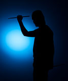 Silhouette Expressive young drummer with drum stick on a blue background Stock Photography