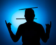 Silhouette Expressive young drummer with drum stick on a blue background Royalty Free Stock Photo