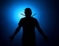 Silhouette Expressive young drummer with drum stick on a blue background Royalty Free Stock Image