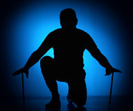 Silhouette Expressive young drummer with drum stick on a blue background.  royalty free stock images
