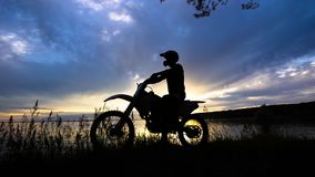 Silhouette of an extreme transport driver who sits on a motorcycle, a vehicle stands near a river on a sunset background stock video