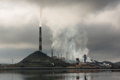 Silhouette of factory with chimneys and heavy smoke.  Royalty Free Stock Photography