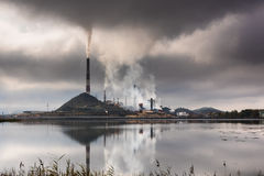 Silhouette of factory with chimneys and heavy smoke.  Royalty Free Stock Images