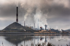 Silhouette of factory with chimneys and heavy smoke.  Stock Images