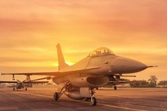 Silhouette falcon fighter jet military aircraft parked on runway in sunset Stock Images