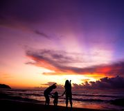 The silhouette of  family. Watching the sunrise on the beach Stock Image