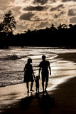 Silhouette of family on the beach at sunset. Silhouette of a family walking on the beach at sunset royalty free stock photos