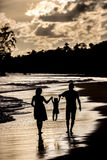 Silhouette of family on the beach at sunset Stock Image