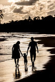 Silhouette of family on the beach at sunset. Silhouette of a family walking on the beach at sunset royalty free stock photo