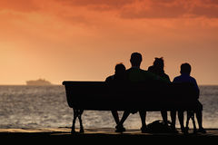 Silhouette of family on a bench by the sea Stock Photos