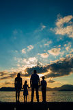 Silhouette of a family with children against the backdrop of the setting sun and sea Royalty Free Stock Photo
