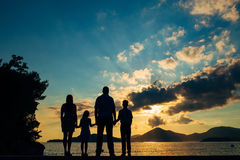 Silhouette of a family with children against the backdrop of the setting sun and sea. In Montenegro Stock Photo