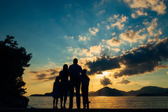 Silhouette of a family with children against the backdrop of the setting sun and sea Stock Images