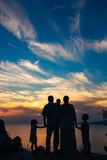 Silhouette of a family with children against the backdrop of the setting sun and sea Stock Photography