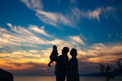 Silhouette of a family with children against the backdrop of the setting sun and sea Royalty Free Stock Photos