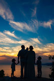 Silhouette of a family with children against the backdrop of the setting sun and sea Stock Photo