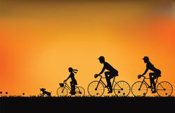 Silhouette of family driving bike with beautiful sky at sunset . Royalty Free Stock Images