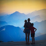 Silhouette of family enjoy the rising sun. Silhouette of family enjoy the light of rising sun in a misty mountain valley Stock Images