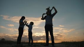 Silhouette of a happy family in the evening in the park. Mom plays with her son and touches his palms. The father is