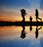 Silhouette family of four. And water Royalty Free Stock Image