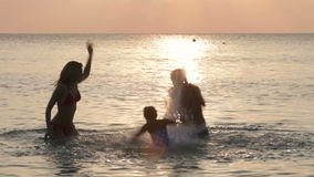 Silhouette Of Family Having Fun In Sea stock footage